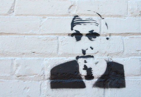 black stencil of a man's head on a white brick wall