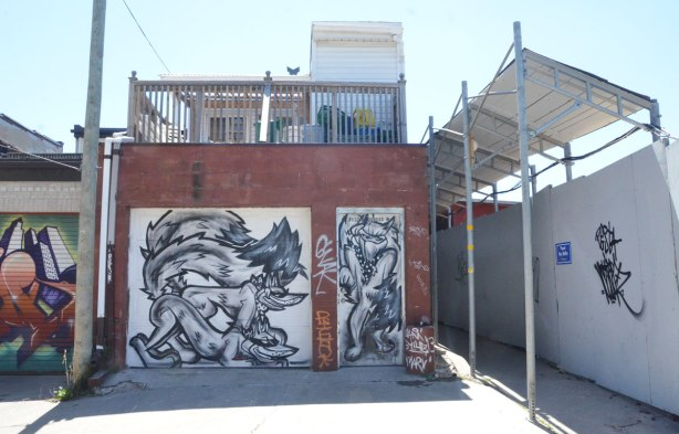 garage door with three black line drawn foxes, there is a construction site to the right of the garage