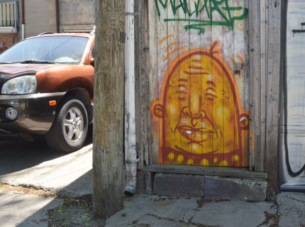 A brown car is parked in a driveway beside a door with a yellow man's face painted on the bottom half of the door. He's bald, little round ears and his eyes are closed.