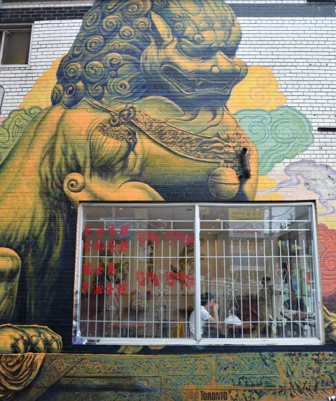 window of a Chinese restaurant with a young man sitting at a table by the window.  On the exterior wall surrounding that window is a painting of a large Chinese lion statue that is part of a larger mural
