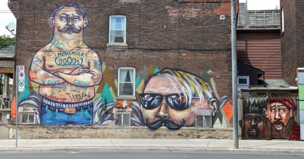 Movember mural on the side of a two storey brick house.  On the left is a man, standing, shirtless with just the top of his jeans showing.  He is tattoed.  Beside him is just the upper part of another man's face, from the large moustache to the top of head with thinning hair.  To the right are two small men's heads, both with moustaches, painted on a wooden fence behind the house. .