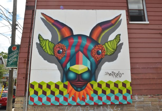 large painting by street artist birdo on the side of a brown clapboard building.   The painting is of the head of a red and blue striped creature with orange horns and lime green ears and nose.