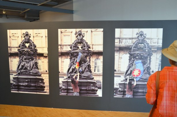 In an art gallery, a series of three large photographs of a statue of Queen Victoria.  THe first picture is just the statue, the middle picture is a man starting to put a  flag over the bottom part of the statue and the third picture is the flag on the statue.  Flag is solidarity flag created by Scott Benesiinaabandan, black and blue background, red circle in the middle, yellow sun in the red circle