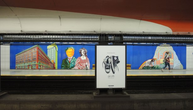 looking across the TTC Queen subway platform and tracks to the opposite wall where there is a mural, enamel on steel, of a couple as well as some buildings. An ad for shoes is blocking part of the mural