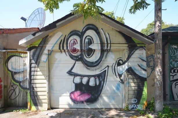A large white spud character on a garage door, with big googly eyes and arms that come out from where his ears are