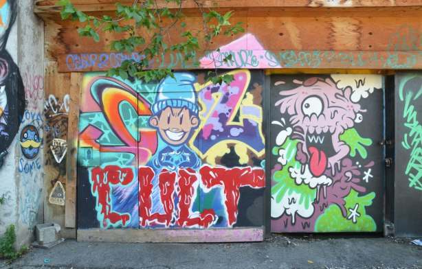 a number of colourful street art paintings on a garage door and gate in an alley