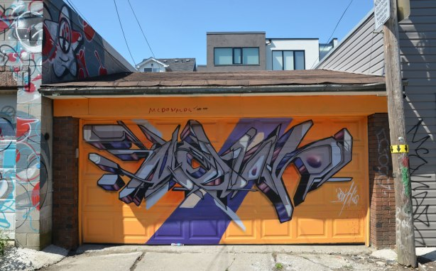 garage door painted orange and then a geometric street art painting in greys and purples painted on that