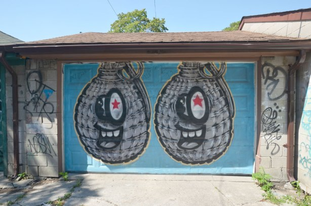 Two spud bomb graffiti characters on a blue garage door in an alley