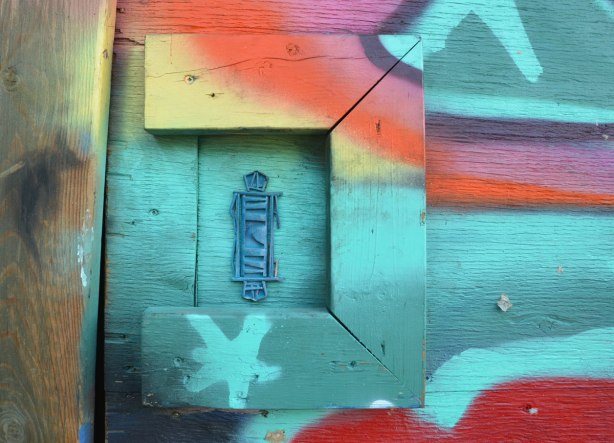 Close up of a graffiti piece, many colours, with a blue 3D stick figure surrounded on three sides by frame-like boards
