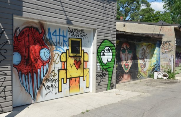 Two garage doors with street art. On the left is a yellow lovebot and a red grominator. On the second is a large woman's face that has been scribbled on as well as a fairy-like creature. The latter two are the work of EGR.An old broken toilet is in the corner.