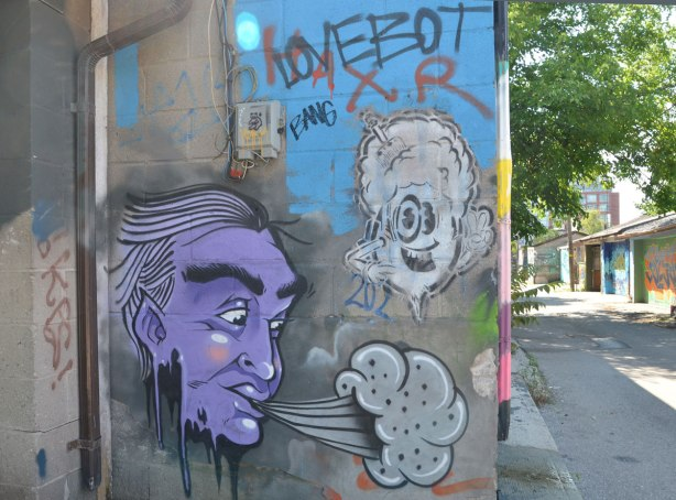 A purple faced man is blowing grey clouds, the alley is in the background.