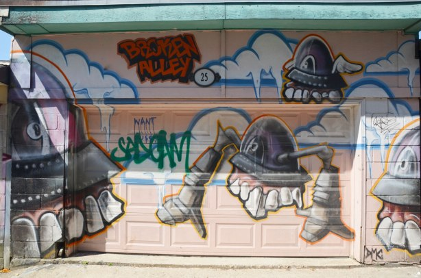 A mural of big headed, big toothed creatures by broken alley on a garage door in a lane.