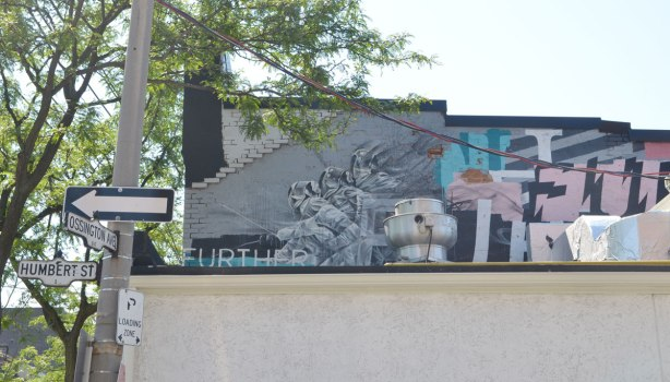 A mural on the upper storey of a building that is partially obscured by items on the roof of the adjacent building. THe theme of the mural is further, and the word further is written many times. There are also images of fencers with their swords.