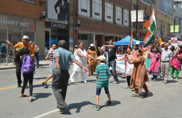 people dancing in a small circle in the middle of Yonge street. They are part of a parade celebrating India's 69th year of independence from Britain. The parade has stopped for a few minutes which has given them time to dance instead of walk.
