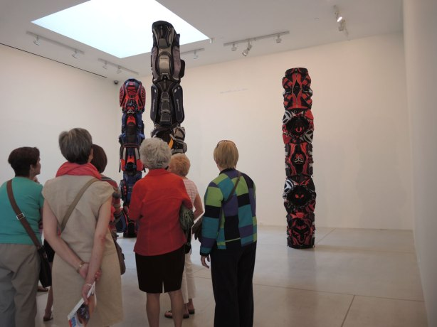 A group of women looks at an art installation of three large totem poles made of golf bags on display in an art gallery (Art Gallery of Ontario)