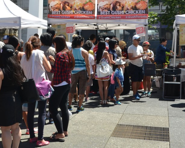 a longline of people waits for food at an outdoor festival at Yonge Dundas Square in Toronto