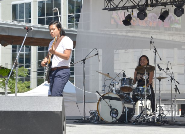 A filipino woman singer and a woman on drums, on a stage, outdoors, making music