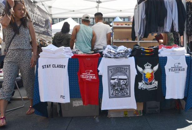 a line of filipino design T-shirts for sale on a table outdoors