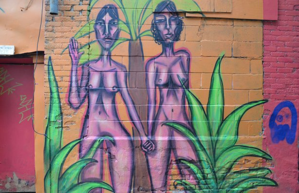 mural street art painting of a naked woman, two pink women holding hands, drawn with purple outlines, on a pink background, with some green plants in the painting too