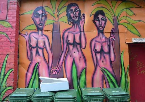 mural street art painting of a naked woman, three pink women standing together, drawn with purple outlines, on a pink background, with some green plants in the painting too