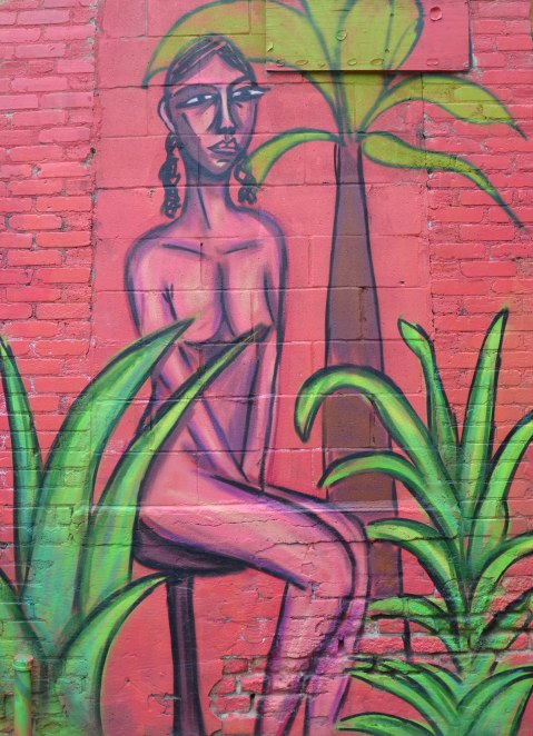 mural street art painting of a naked woman, pink woman with purple outlines, on a pink background, with some green plants in the painting too