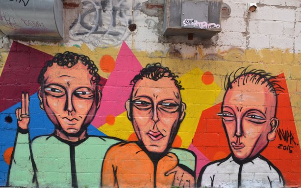 mural street art of three men from the waist up. All have short hair, one with green shirt, one with orange shirt and the third with a white shirt,