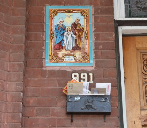 A ceramic plaque of Mary, Joseph and Jesus on the exterior wall of a house beside the front door and above the mailbox