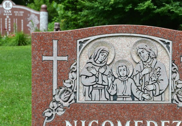close up of part of a tombstone in a cemetery showing a small relief sculpture of Mary, Joseph and Jesus