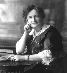 black and white picture of a woman, Nellie McClung, sitting at a desk