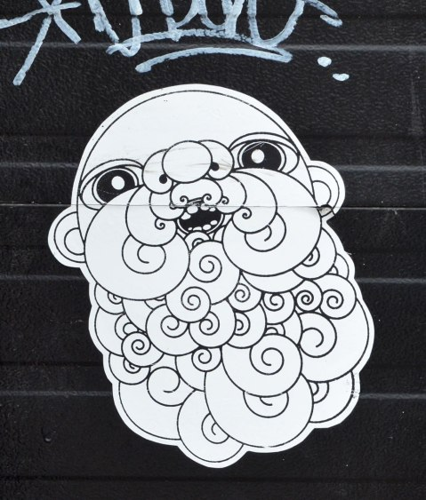 Black and white wheatpaste of a man's head, bald but with a large curly beard. Line drawing