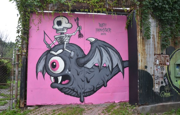 A garage door in an alley painted pink. A large fat grey creature with bat-like wings and bulging eye takes up most of the space, a small skeleton is sitting on the creature's head. The piece is signed Buff Monster