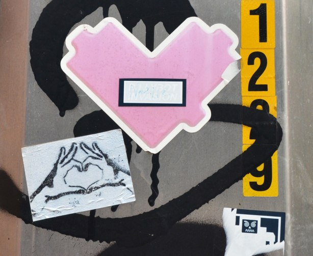 Two heart stickers on a metal pole. One is a pink lovebot shaped heart and one is a drawing of two hands making a heart shape with the thumbs and forefingers