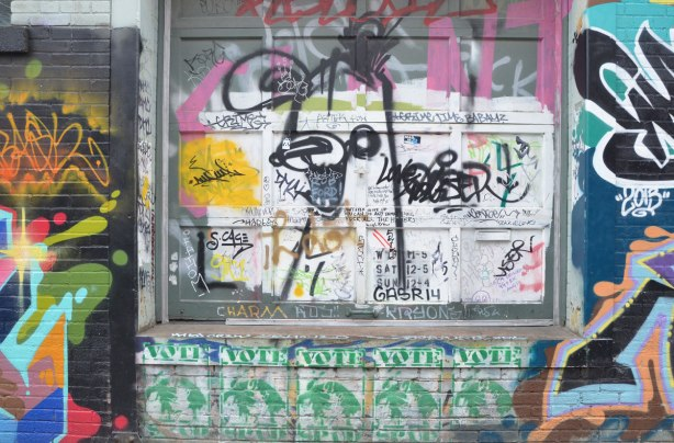 A black poser bunny spray painted on a wall that is covered with slaps, stickers, and words written in black marker