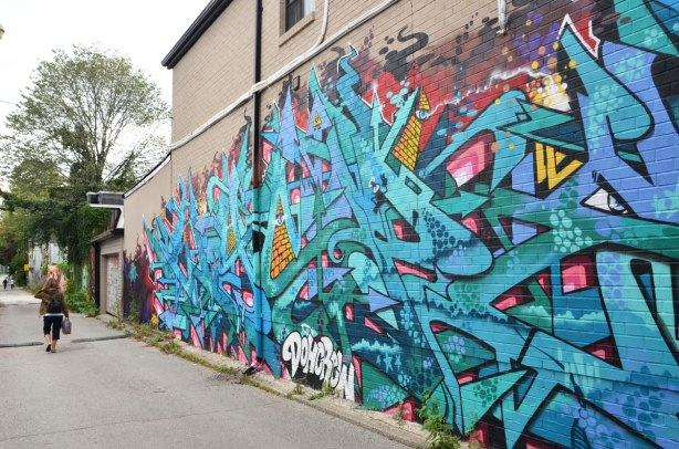 A large street art piece painted in an alley. It covers most of the side of a brick house. It is mostly blue lines and arrows.