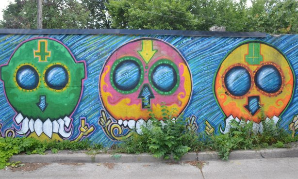 3 big round headed aliens by street artist mska, one is green, one is pink and yellow and one is yellow and orange, on a fence in an alley