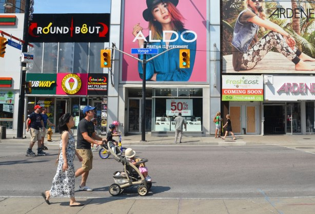 A couple is pushing a stroller up Yonge St. past some of the stores. No cars on the street