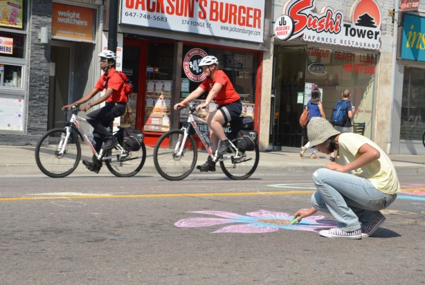 Two men wearing red T shirts are riding their bikes on Yonge street, passing a woman who is using chalk to draw a floor on the street
