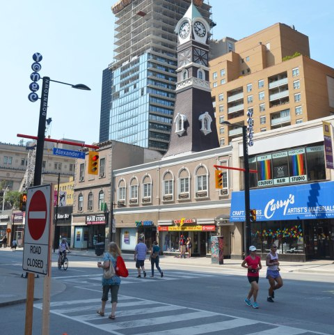 Two women are jogging, and other people are walking, on Yonge street on a Sunday morning at Open Streets Toronto so there is no traffic.