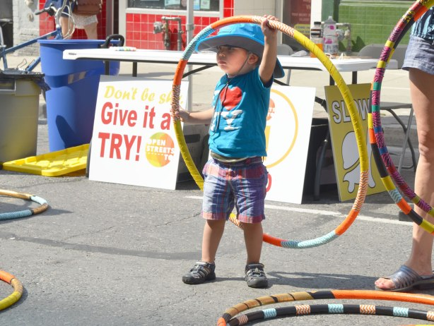 A young boy is playing with a hula hoop in front of a sign that says Give It a Try