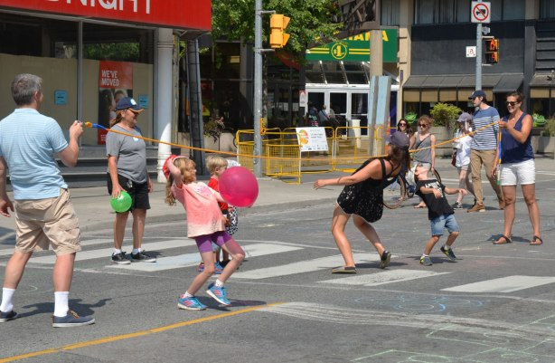 A group of adults and kids are doing the limbo with a long rope on the street on a day when the road is closed to traffic.