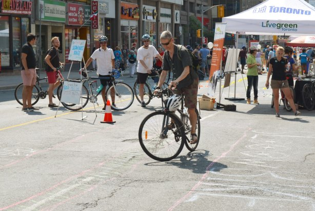 A man is riding his bike as slowly as possible and still stay within a narrow path as part of a slow bike race. Other people are standing beside their bikes and watching him