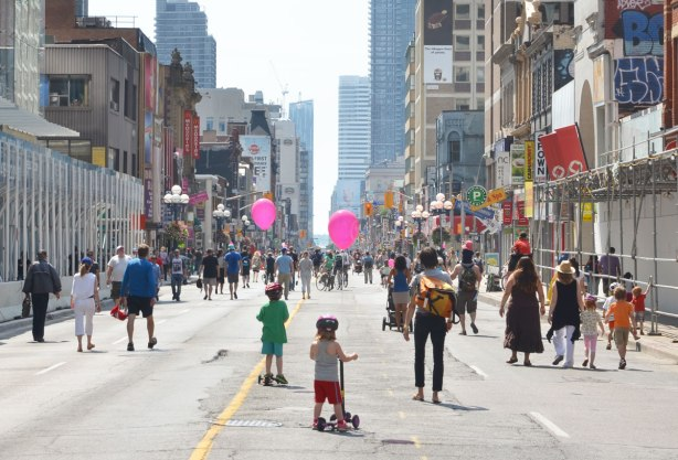looking south on Yonge St. from Bloor street on a morning when no cars allowed. There are people walking on the street. There are also two kids with pink balloons.