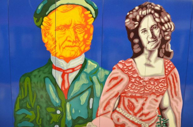 mural on a subway wall, close up of a man and a woman. The man has an orange coloured face and is wearing a green jacket and cap. The woman has long black hair and a long pink dress