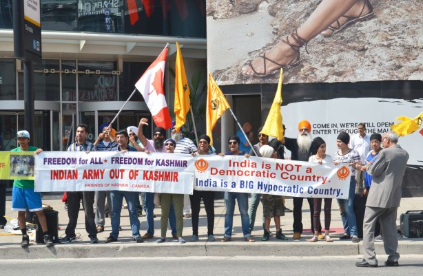 A protest is held on Yonge street by Dundas subway station entrance. A group of Sikhs is protesting the presence of the Indian army in Kashmir. They have two banners and some flags including a Canadian flag. They represent the group, Freedom of Kashmir, Canada.