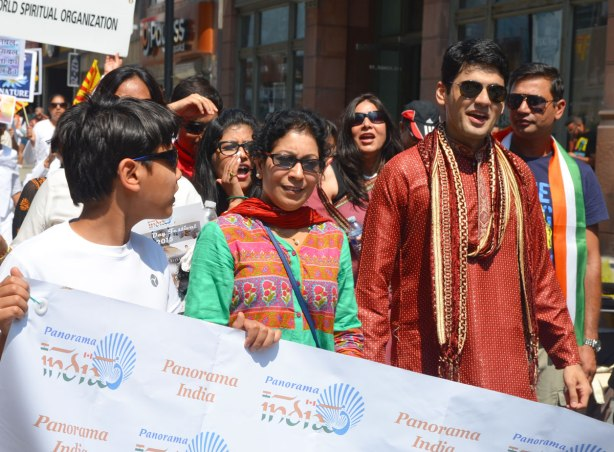 A group of people are walking in an India independence day celebration parade, they are holding a banner and walking behind it.