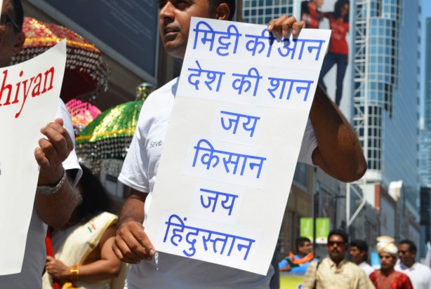 A man is holding up a sign with words written in Hindi