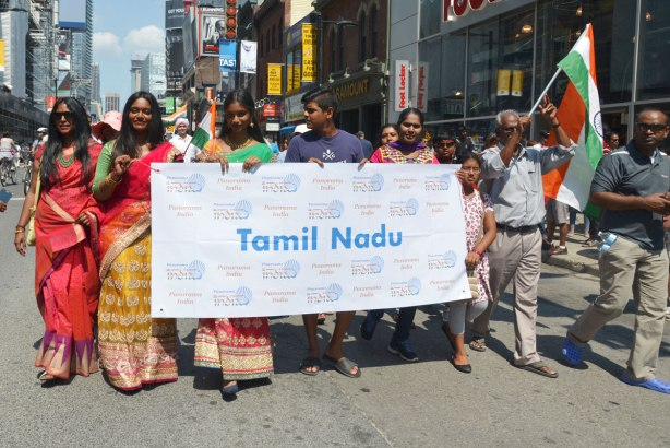 A group of people walk behind a banner that says Tamil Nadu. This is a state in India and the parade is to mark Indian independence day. The women are wearing colourful saris