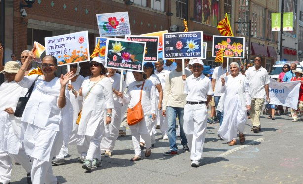 A group of marchers in a parade all wearing white clothes and carrying signs promoting peace and love and understanding and all those good things