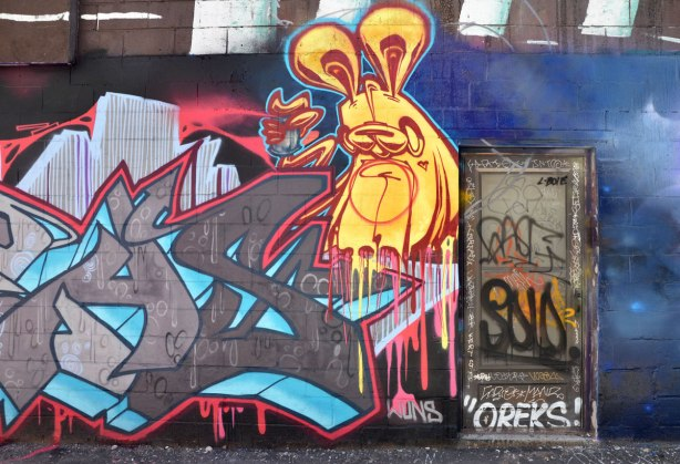 a yellow poser bunny on a wall in an alley beside a door that is covered with tags including oreks