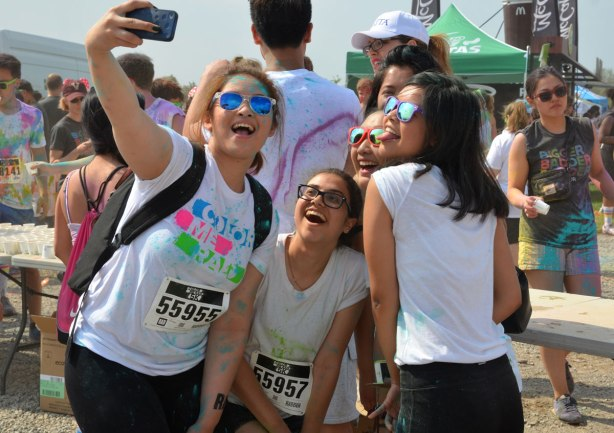A group of four young women are taking a selfie just before running in the colour me rad race